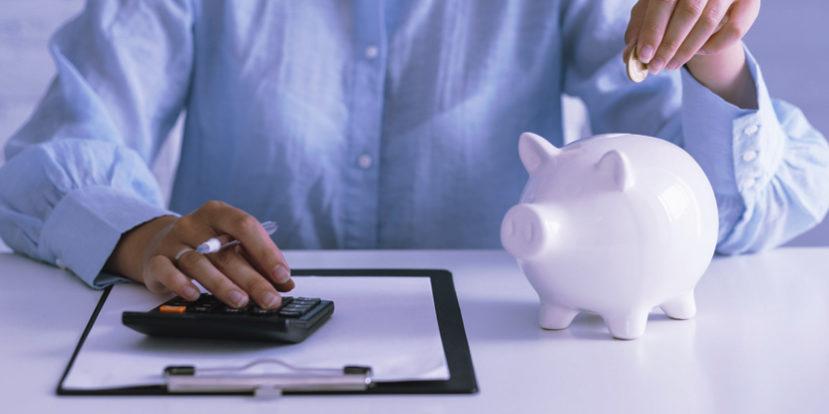 Άντρας με το ένα χέρι πληκτρολογεί σε κομπιουτεράκι υπολογισμών και με το άλλο τοποθετεί νόμισμα σε κουμπαρά
